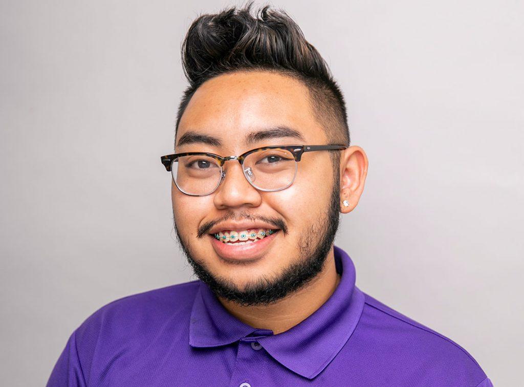 Headshot of young man wearing glasses smiling named John Nguyen.