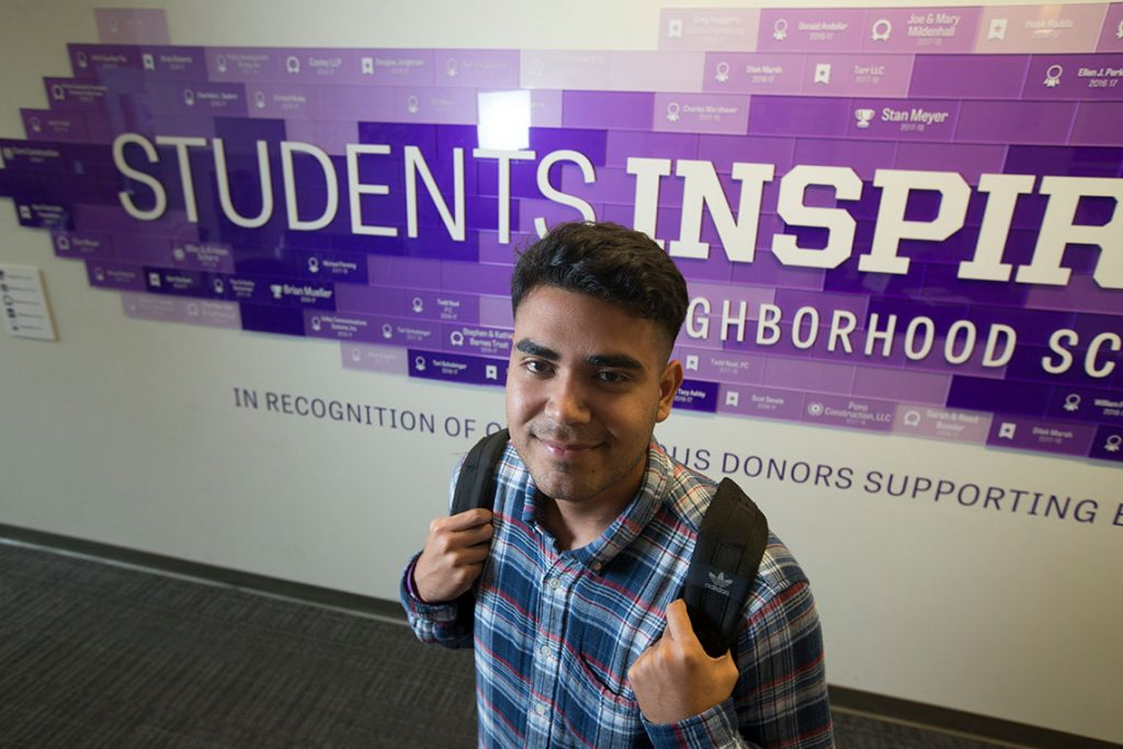 Young man named Jose Monarrez smiling in front of SIS sign.