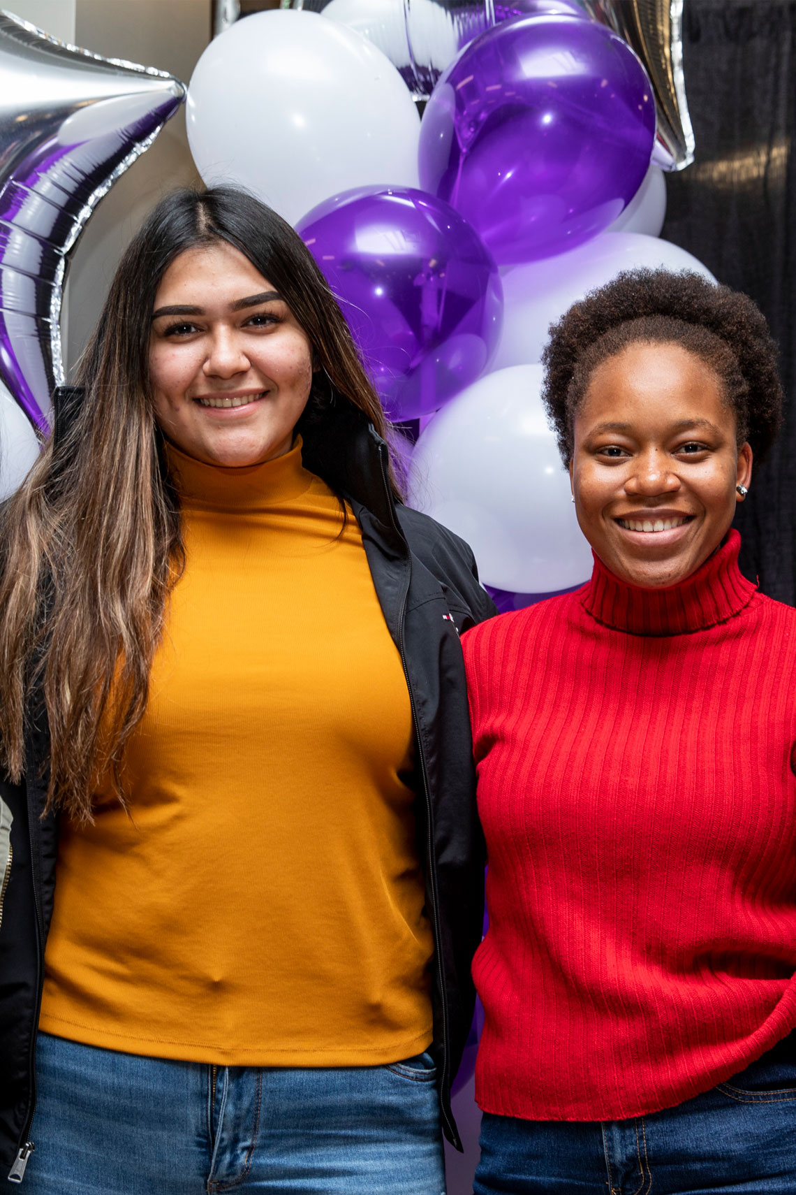 Two young women smiling in front of purple and white balloons.