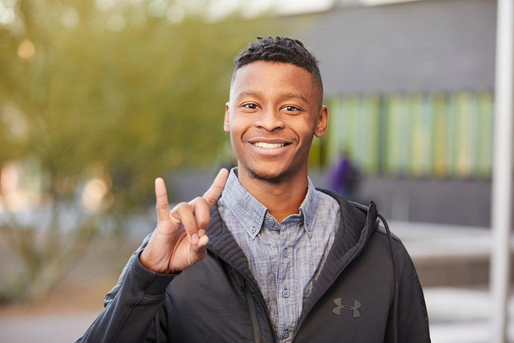 Young man smiling outside giving a lopes up gesture with his hand.