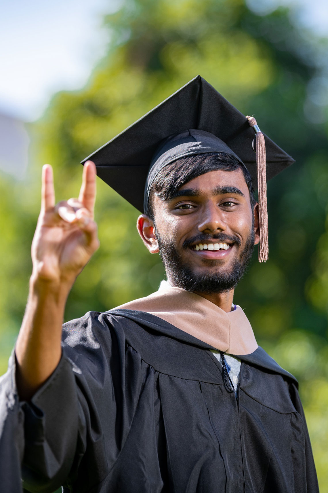 Young man outside in graduation garb giving lopes up gesture and smiling.