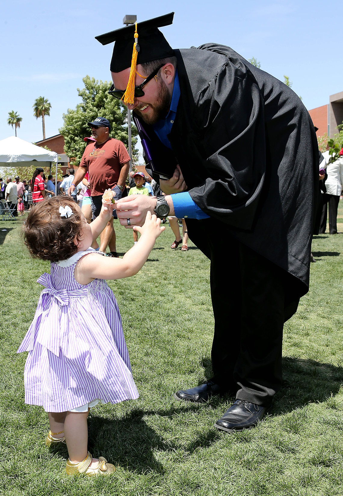 Recently graduated male students hands a flower to a little girl outside.