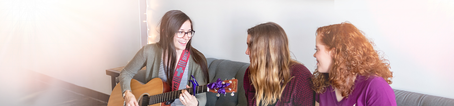Three young women sitting on couch with guitar.