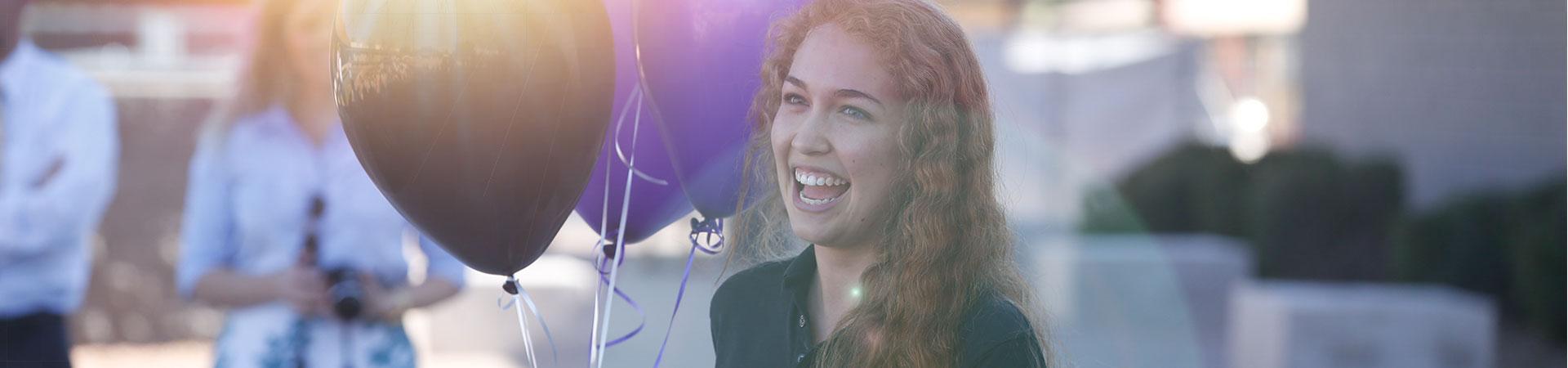 Girl smiling holding balloons