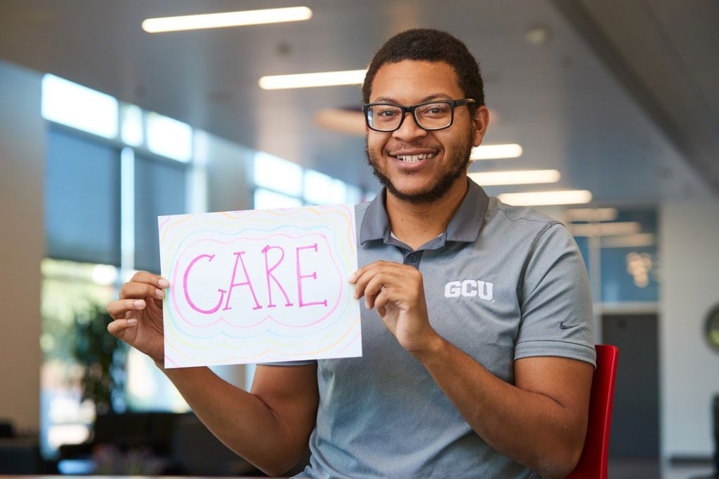 """Student holding a sign that says """"Care"""""""
