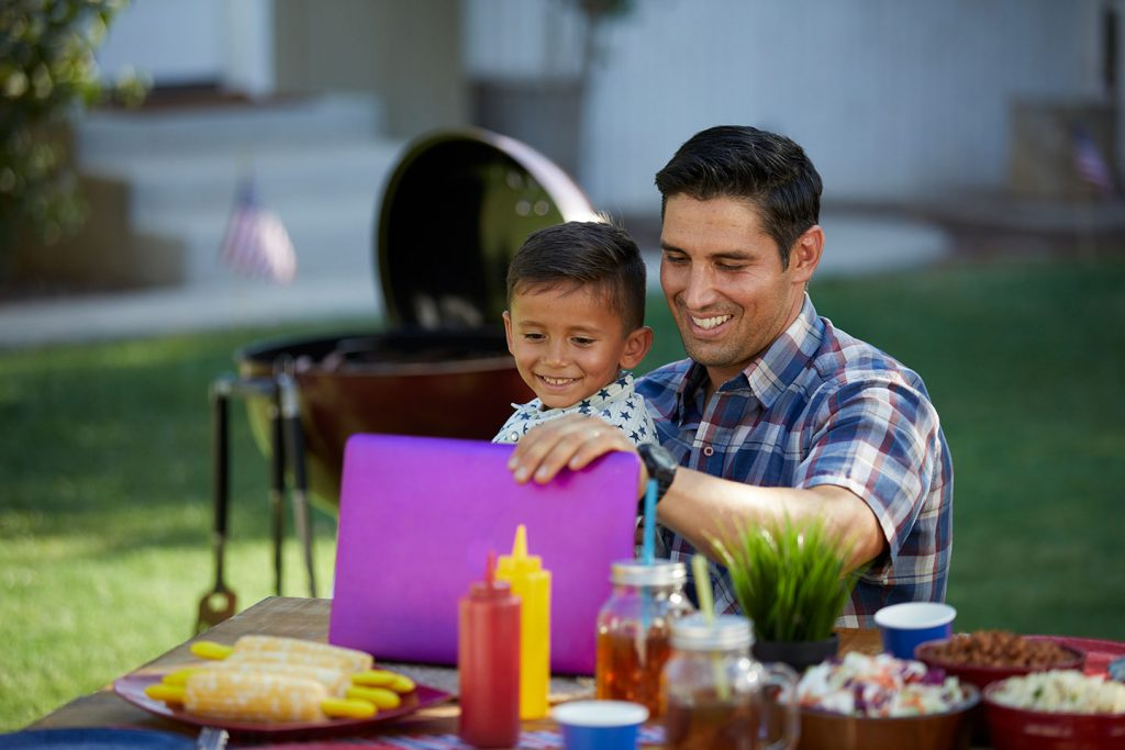 Father and son smiling while working on laptop outside.